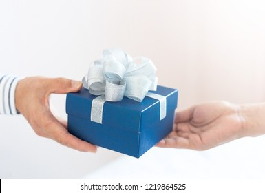 close up of young man give a gift in a box,holding blue Gift box with bow over holiday background which celebrating  couple at home