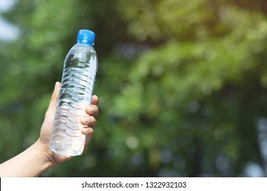 close up young man Hand holding fresh drinking water bottle from a plastic in the park.