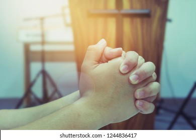 Close up of a young man hands praying to God in front of The pulpit with show Jesus cross over blurred music instrument at christian local church
