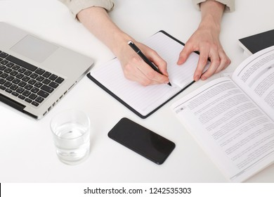 Close up of young man hands writing notes, making abstract, summary, opened a notebook on the table, there is a laptop near by, glass of water, phone with black screen, book and notebook