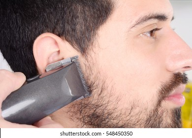 Close up of young man having a beard cut with hair clippers.
