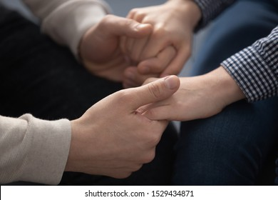 Close up young man holding hands of wife, showing support and love. Married couple reconciled after family quarrel or misunderstanding. Husband comforting beloved woman, overcoming problems together.