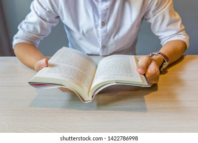 Close up of young man holding reading book