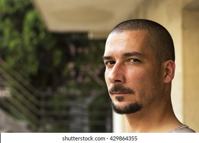 Close up of young man looking at camera in front of the house
