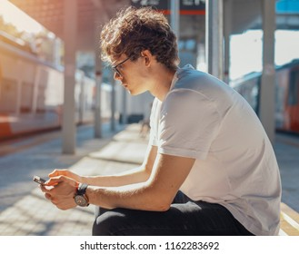 Close up of young man looking at mobile phone screen at metro station.