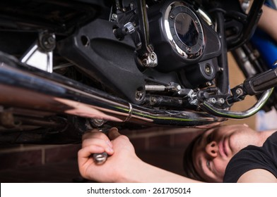 Close Up of Young Man Mechanic Working on Adjustments to Under Side of Motorcycle