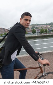 Close up or a young man riding on a bike on a cloudy day near the river with a shoulder bag and jeans