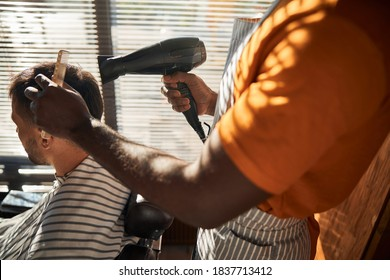 Close up of young man sitting in barber chair while hairdresser styling his hair with hair dryer and comb