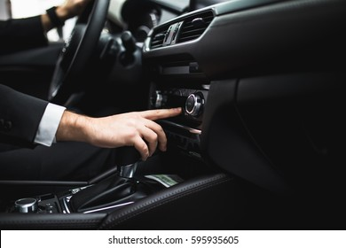 close up of young man in suit driving car and switching some button on panel of car