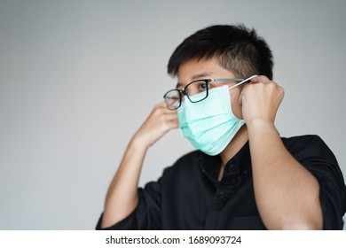 Close up  the young man wearing face hygienic mask for prevention global covid-19 virus pandemic. The corona-virus from Wuhan is dangerous. People need quarantine.