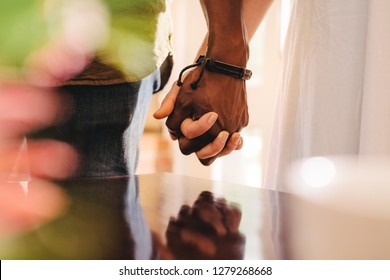 Close up of young man and woman holding hands. Cropped of interracial couple on date holding hands, focus on hand in hand.