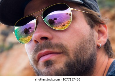 Close up of a young man's face wearing reflective sunglasses