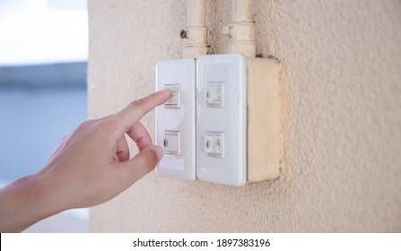 Close up young man's hand pressed the button to turn on the light switch, Open the electrical circuit beside the wall.