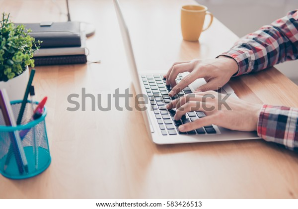 Close up of young man's hands working and searching for information on the Internet
