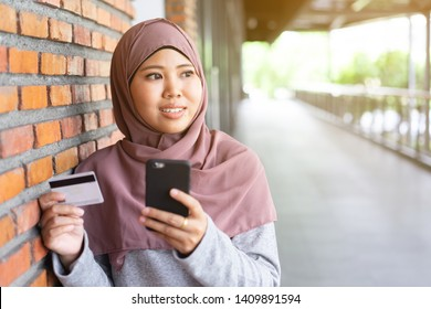 close up young muslim asian woman holding smartphone and credit card for online shopping at outside apartment in relax time on weekend, lifestyle people concept