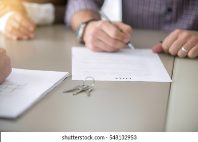 Close up of young people got access to home ownership signing a bank loaning, mortgage program, bound with a loan, buying a home as a good option, couple meeting with bank worker or real estate agent