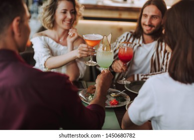 Close up of young people sitting at the table and clinking glasses of alcoholic drinks. Focus on hands with drinks
