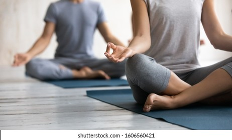 Close up young people wearing sportswear practicing yoga at group lesson, sitting in Easy Seat pose with mudra on mats, doing Sukhasana exercise, stress relief, working out in modern yoga center club
