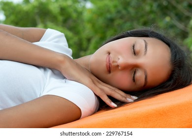 Close up Young Pretty Asian Indian Woman Relaxing on Beach Chair with Orange Towel While Eyes are Close.