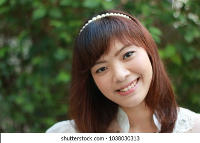 Close up of young pretty Asian woman in white dress with garden background.