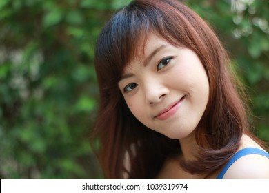 Close up of young pretty Asian woman in blue dress with garden background.