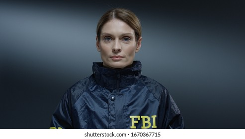 Close up of the young pretty Caucasian woman, FBI worker rising her face and siling happily straight to the camera. Portrait.