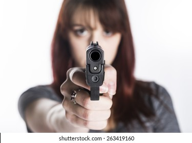 Close up Young Pretty Woman Pointing a Gun at the Camera with One Hand, Isolated on White Camera.