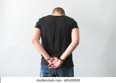 Close up of young prisoner get arrested by wearing handcuffs, isolated on white background