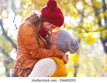Close up of young romantic couple on a sunny autumn day in the park. They express tenderness.