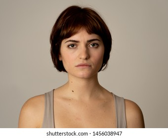 Close up of a young sad woman, serious and concerned, looking worried in emotional pain. Feeling sorrow and depression. Isolated in neutral background. In facial expressions and emotions concept.
