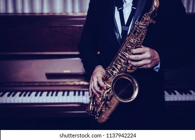 close up of Young Saxophone Player hands holding alto sax musical instrument with piano background in dark room, vintage tone, can be used for music background, copy space