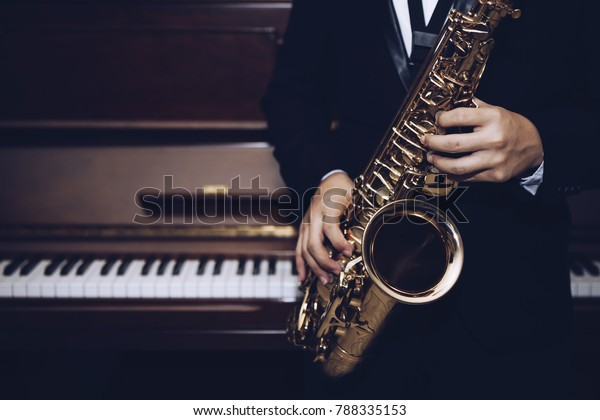 close up of Young Saxophone Player hands  playing alto sax musical instrument over the piano  background,  closeup with copy space, vintage tone,  can be used for music background