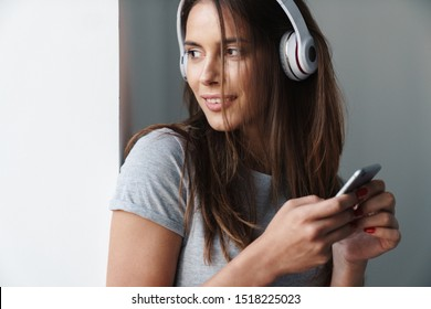 Close up of a young smiling beautiful girl standing leaning on a gray wall over gray background, listening to music with wireless headphones while holding mobile phone