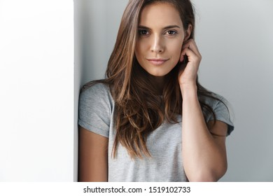 Close up of a young smiling beautiful girl standing leaning on a gray wall over gray background, looking at camera