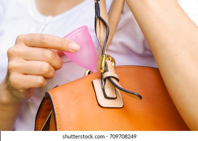 Close up of a young smiling beautiful woman keeping a menstrual cup inside of a purse. Gynecology concept