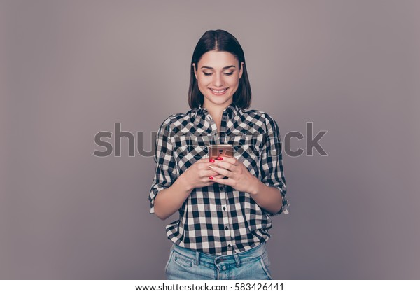 Close up of young smiling lady typing sms on her smartphone against gray bachground