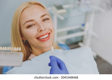 Close up young smiling woman choosing veneers enamel color palette with stomatologist compare teeth shade sit at dentist office chair indoor light modern cabinet Healthcare enamel whitening treatment