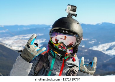 The close up of a young snowboard girl wearing ski googles with a spectacular mountain view behind her.
