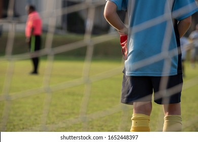 Close up of a young soccer goalie goalkeeper during the match. Youth Soccer game on a sunny summer school tournament Day. Football match going on in a background. View from behind the net.