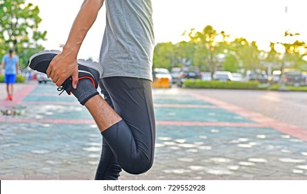 Close up young sport man is stretching leg muscle to prevent injury before exercise or running, good performance, flexibility, warm up, in morning time with sunrise at city park