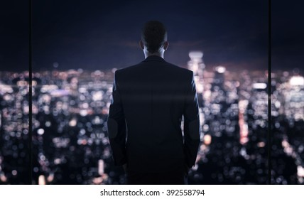 Close up of young successful businessman looking at the the city at night