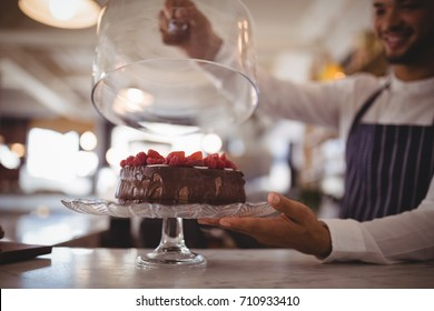 Close up of young waiter holding glass lid over cake on cakestand at counter in coffee shop