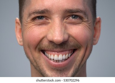 Close up young widely smiling man, gray background