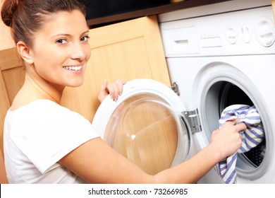 A close up of a young wife putting a cloth into washing machine