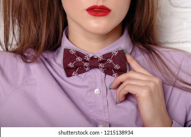 Close up of young woman adjusting her bow tie in red shirt. Elegant girl model poses in blouse and bow tie. Close-up portrait of young beautiful lady holding bow-tie. Advertising photo, sale, discount