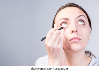 Close up Young Woman Applying Eyeliner Makeup on her Lower Eyelid While Looking Up Seriously on a Gray Background.