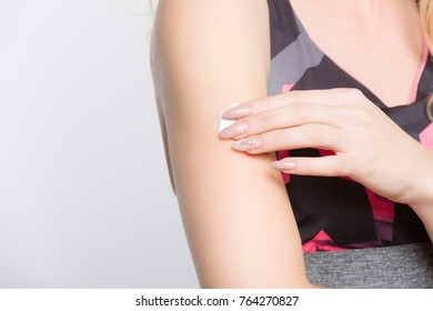 close up of a young woman applying skin cream on her arm