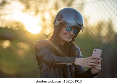 close up of Young woman biker with helmet jacket and motorcycle glasses video with mobile phone at sunset