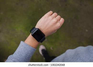 Close up of young woman checking the smartwatch device, outdoors.