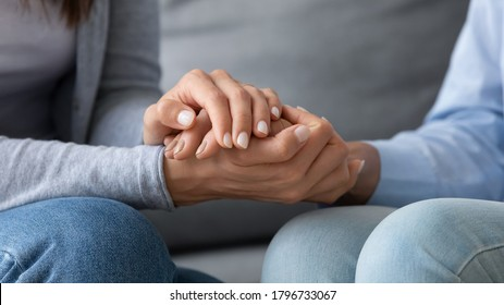 Close up young woman covering hands of mature senior mother, asking for forgiveness, feeling guilty, apologizing indoors. Compassionate grownup daughter comforting supporting retired mum at home.
